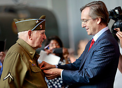06 June 2014. The National WWII Museum, New Orleans, Lousiana. <br /> WWII veteran Pfc Horace Calhoun, Company K, 116th Infantry, 3rd Battalion is presented with the French Legion of Honor medal by the French Consul General Jean Claude Brunet. <br /> Photo; Charlie Varley/varleypix.com