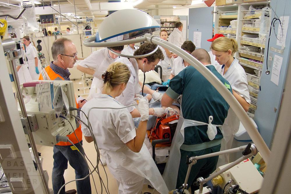 Artsen en verpleegkundigen stabiliseren in de 'rode sluis', de plek waar de zwaarst gewonden het eerst worden geholpen, een slachtoffer.In het Calamiteitenhospitaal in Utrecht wordt een rampenoefening gehouden. De nadruk ligt op de contaminatie, door een gekantelde vrachtwagen zijn veel slachtoffers in aanraking gekomen met een chemische stof. Voor het eerst wordt er geoefend met een zogenaamde decontaminatietent. Als de tent bevalt, schaft het ziekenhuis zo'n tent aan. Bij de 'ramp' zijn 100 slachtoffers gevallen.<br /> <br /> Doctors and nurses are treating a 'victim' in the red zone, the area where the worst injured are being stabilized. In the Trauma and Emergency Hospital in Utrecht an calamity training was held. The emphasis is on the contamination by an overturned truck, many victims are contaminated by a chemical. For the first time a so-called decontamination tent was used. If the tent fulfills the expectations, a tent will be purchased. The 'calamity' caused 100 victims.