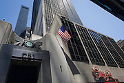 The East River Savings Bank in Lower Manhattan, New York City. Walking across Church Street they go beneath two American flags of the bank at the corner of 26 Cortlandt Street. Seen from a low angle, we look upwards to a tall skyscraper that rises into the Manhattan sky, adjacent to the site of the former Twin Towers and Ground Zero. It symbolises a wealthy country whose people largely enjoy a prosperity and stability of both economy and government.