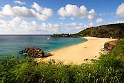 The calm summer waters of Waimea Bay on the North Shore of Oahu, Hawaii.