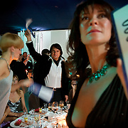 """Rustam Tariko, billionaire oligarch owner of the vodka brand """"Russian Standard"""", waves mock dollar bills to pledge donation during a charity ball in Moscow."""