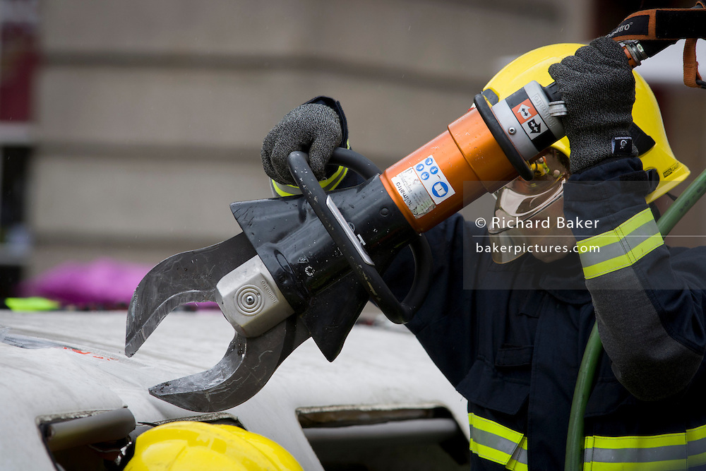 Firefighters from the London Fire Brigade's 'extrication' team using a using a Holmatro dedicated cutter to demonstrate how firefighters rescue passengers by cutting open a stretch limousine in London's Covent Garden Piazza. Highlighting the dangers of hiring illegal luxury or novelty cars, this vehicle was seized last year with many mechanical defects rendering it unsafe for those inside with limited exit doors. Of 358 cars stopped in March 2012, 27 were seized and 232 given prohibitions. This scenario is a simulation and therefore reproduces the reality of an emergency, using real emergency services personnel and equipment. Casualties are volunteers and none were injured in the making of this photograph.