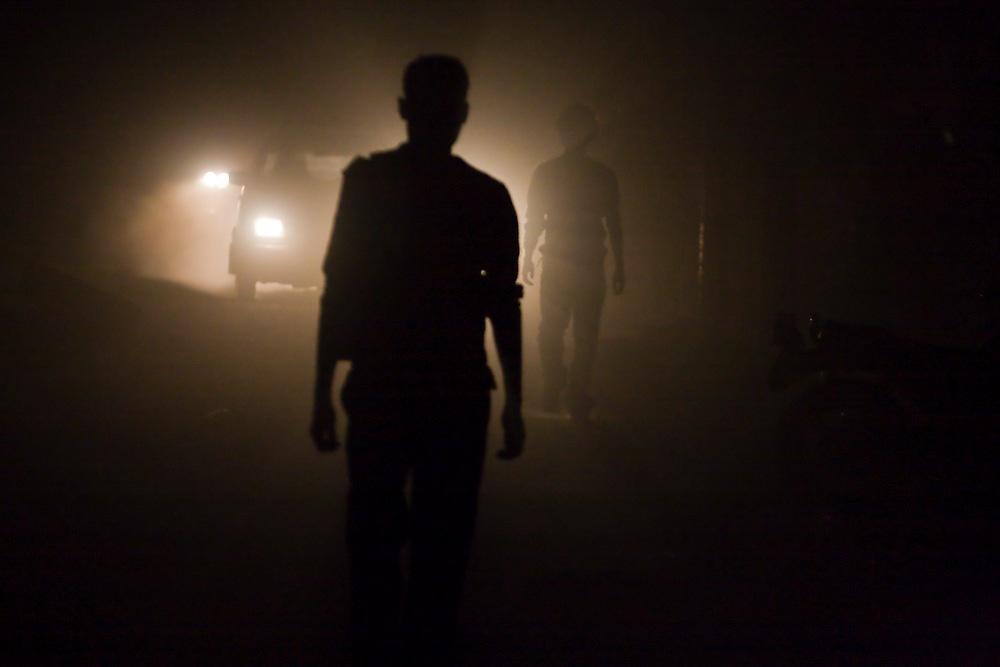 Young men, backlit by car headlights, walk down a dusty street in Boudhanath, Kathmandu, Nepal.