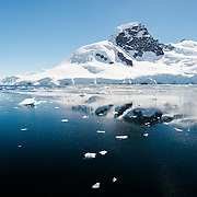 A scenic landscape on the Antarctic Peninsula on a calm sunny day near Cuverville Island, Antarctica.