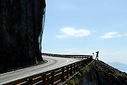 Near-silhouette of tourist standing on edge of cliff, outside safety fence, taking photograph. Biokovo National Park, near Makarska, Croatia