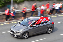 Fans fly a Liverpool flag out of the car window as they wait for the team bus to arrive for the Champions League Winners Parade in Liverpool. **Please note numberplate has been pixelated by picture desk***