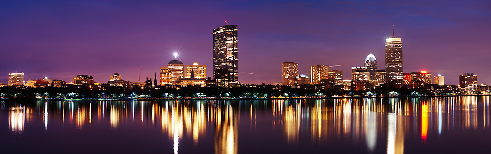 The Boston skyline shimmers in the waters of the Charles river as dusk begins to settle over the city. As seen from Cambridge.