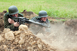 Renactors portray German troops manning an MG42 machine gun from a pre prepared dug in position during a world war two battle reenactment at the Spam Wartime Weekend in Heckmondwyke<br /> June 2011