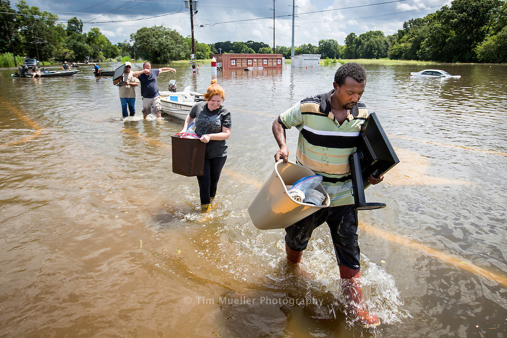 Volunteer Raymond Daby, right, helps carry Catrina Chmurka's household items to her vehicle parked on Airline Highway. Dozens of boats carried residents, their pets and belongings to the intesection of Airline Highway and Highway 431.