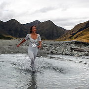 Runner Liat Saad crosses  Moke Creek on the Ben Lomond High Country Station during the Pure South Shotover Moonlight Mountain Marathon and trail runs. Moke Lake, Queenstown, New Zealand. 4th February 2012. Photo Tim Clayton