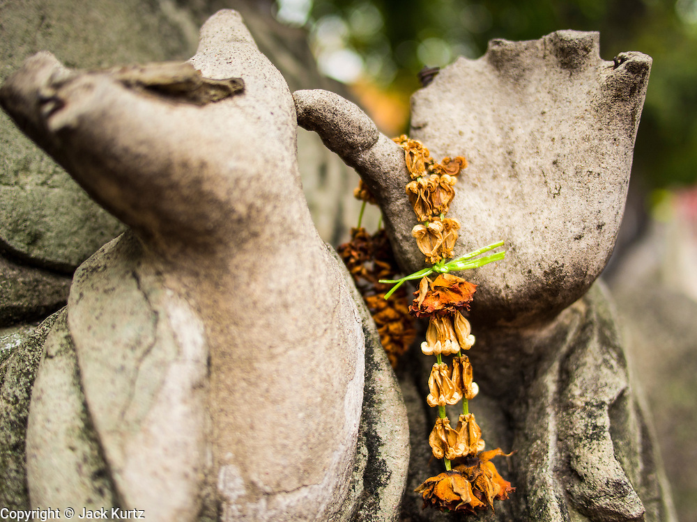 "21 JULY 2013 - BANGKOK, THAILAND: A wilted garland on a Buddha statue at Wat Benchamabophit, the ""Marble Temple"" in Bangkok, Thailand.          PHOTO BY JACK KURTZ"