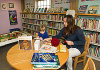 Maximillion and Eileen McMenamon spend time together working on puzzles and knitting in the Gilmanton Year Round LIbrary on Wednesday morning.  (Karen Bobotas/for the Laconia Daily Sun)