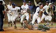 The Panthers rush the field after FIU pinch-runner Kolby Follis (14) slides home to score around Miami catcher Joe Gomez (40) in the bottom of the ninth inning to give FIU a 3-2 victory over the University of Miami. FIU's Nick Day's two-base sacrifice fly deep to center drove home Folli at FIU Baseball Stadium University Park on Wednesday, March 8, 2017.