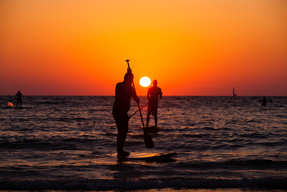 Paddleboarders are silhouetted during sunset at the Mediterranean Sea near Gordon Beach in Tel Aviv, Israel, on July 21, 2015.