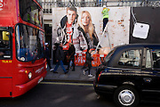 A large fashion advertising billboard stands above traffic, pedestrians and workmen fitting lights on the hoarding.