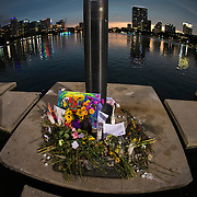 Flowers, candles and homemade signs surround a small makeshift memorial at Lake Eola park flagpole for the victims of the Pulse nightclub where many victims were killed in the deadliest shooting in modern U.S. History on Tuesday, June 14, 2016, in Orlando, Fla. (Alex Menendez via AP)