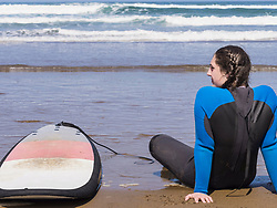 Woman relaxing with surfboard at Sopela Beach, Biscay, Basque Country, Spain