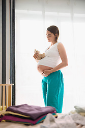 Pregnant woman holding stomach baby cot