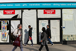 © Licensed to London News Pictures. 19/10/2020. London, UK. Shoppers in north London walk past a store which has closed due to coronavirus crisis. According to the figures, revealed by the Local Data Company and advisory firm PricewaterhouseCoopers (PwC), a total of 11,120 shops on UK high streets closed in the first half of this year due to the coronavirus lockdown.  Photo credit: Dinendra Haria/LNP