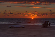 The sky turns a dramatic  orange and blue as the sun rises above the hotizon. The silhouetes of two people watching the sunrise are visible by the life guard chair.
