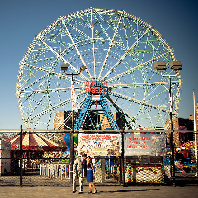 Two lovers kiss in front of Coney Island's big wheel, Brooklyn, New York, 2010.