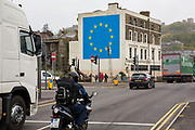 Graffiti artist Banksy has unveiled his latest piece about Brexit in Dover, United Kingdom. The artwork shows a man up a ladder chipping a gold star away from the EU flag. The piece appears on the wall of a derelict building directly adjacent to the A20 road less than half a mile to the ferry terminal of Dover.