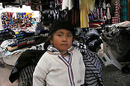 A  young girl poses for a portrait  at the Plaza de Ponchos  Market, Otavalo, Ecuador.