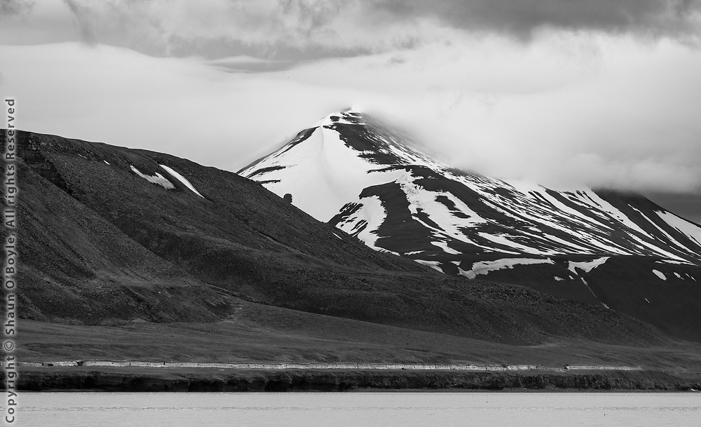 Isfjorden shoreline at Rusanovodden. Just above the shore line is a wood enclosed narrow gauge rail line that ran from Grumant to Colesdalen and was used to transport coal. The mountain beyond is Smasyskena.