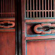 Decorated red wooden folding doors at the Temple of Literature in Hanoi. The temple was built in 1070 and is one of several temples in Vietnam which are dedicated to Confucius, sages and scholars.