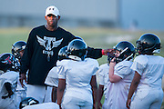 Deion Sanders coaches kids during football practice for Truth, a non-profit sports organization Sanders founded, at the Prime Prep Academy campus in Dallas, Texas on August 6, 2014.