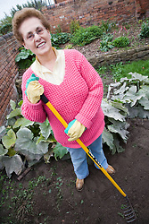 Older woman gardening in a garden,