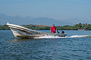 A fisherman motors his panga in Lake Catemaco, Veracruz, Mexico. The lagoon which flows into the Gulf of Mexico is one of the best preserved coastal wetlands and mangroves forests in Mexico and part of the Los Tuxtlas biosphere reserve.