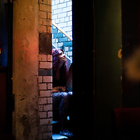 Manchester, UK - 4  August 2012: a girls sits on the stairs of the Temple Bar