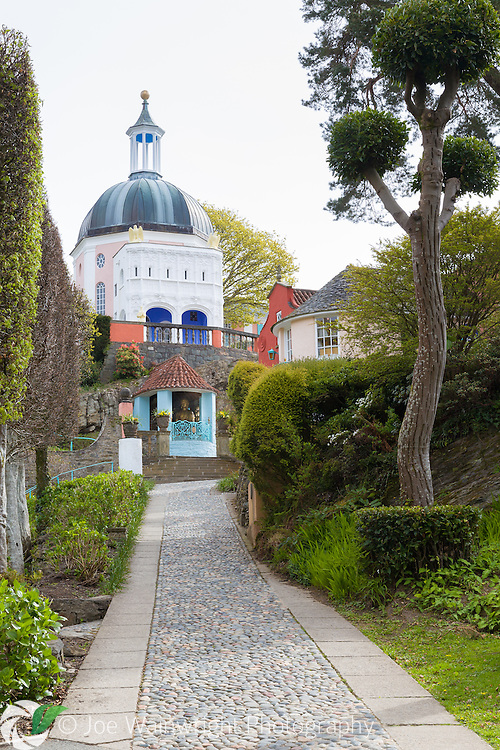 The Italianate village of Portmeirion, Gwynedd, is located on the estuary of the Dwyryd. It was built by Sir Clough Williams- Ellis between 1925 and 1975. Around the many colourful and unusual buildings are attractive garden areas and borders. In addition, the Gwyllt wild gardens cover the neighbouring hill and run down to the sea. They were developed by Caton Haig, an expert on Himalayan flowering trees. On his death in 1941 Clough incorporated the Gwyllt gardens into the village.  They include tall conifers, tree ferns and large rhododendrons. There are also a number of lakes, with the largest spanned by a by a Chinese bridge, with a temple sited on the hillside above.