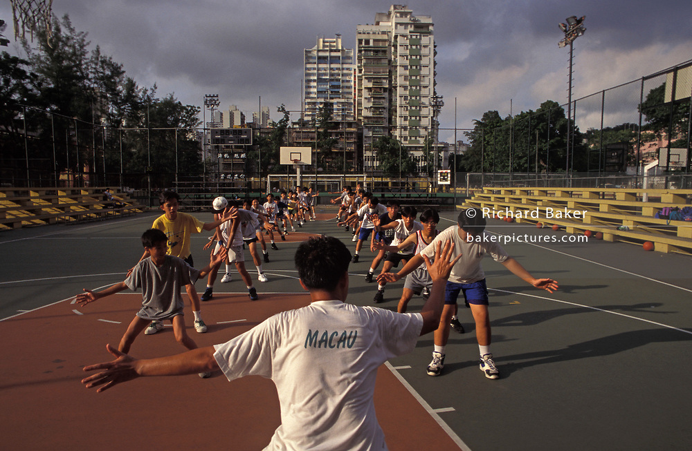 An exercise class for schoolchildren on a basketball court at a sports ground in the highly-populated Asian city, on 10th August 1994, in Macau, China. Macau is now administered by China as a Special Economic Region (SER), home to a population of mainland 95% Chinese, primarily Cantonese, Fujianese as well as some Hakka, Shanghainese and overseas Chinese immigrants from Southeast Asia and elsewhere. The remainder are of Portuguese or mixed Chinese-Portuguese ancestry, the so-called Macanese, as well as several thousand Filipino and Thai nationals. The official languages are Portuguese and Chinese.