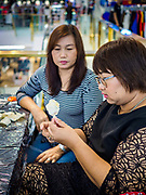 "24 MAY 2017 - BANGKOK, THAILAND: Women at the Emporium, an upscale shopping mall in Bangkok, make wooden roses to be used during the cremation of Bhumibol Adulyadej, the Late King of Thailand. In Thai culture it is customary to place wooden flowers in front of a deceased person's coffin or urn as a last tribute before cremation. The Royal Cremation Organisation Committee, which is overseeing plans for the cremation of Bhumibol Adulyadej, the Late King of Thailand, asked the Bangkok Metropolitan Administration (BMA) to provide three million wooden flowers for the late King's cremation. The BMA, in turn, has asked malls and civic organizations to provide flowers. The Mall Group, which owns Emporium, has pledged to provide up to one million wooden ""Wiangping"" roses, which in Thai culture symbolize unconditional love. The late King will be cremated October 26, 2017.     PHOTO BY JACK KURTZ"