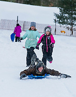 Autumn Boisvert and Jasmin Boisvert chase Caleb Cox down the sledding hill at the Gilford Outing Club on Tuesday afternoon.  (Karen Bobotas/for the Laconia Daily Sun)