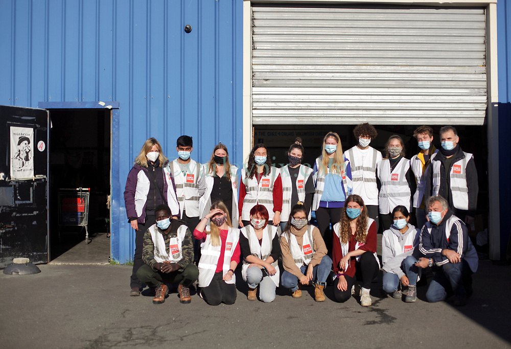 18 November 2020. Care4Calais - Calais, France.<br /> Claire Moseley, (at left) founder of the volunteer run migrant refugee charity Care4Calais and her team of volunteers outside their distribution centre near Calais. The charity provides meals, clothing, haircuts, charging stations for phones, hot drinks, tents, blankets and a wide range of goods and services to help migrant refugees struggling to survive on the streets of Calais where they are continually harassed and moved on by authorities. <br /> Photo©; Charlie Varley/varleypix.com