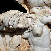 Close up of Roman Sebasteion relief  sculpture of Nero conquering Armenia depicting a fallen female representing Armenia,  Aphrodisias Museum, Aphrodisias, Turkey.    Against a black background.<br /> <br /> Nero, wearing only a cloak and sword strap, supports a slumped naked Armenia by her upper arms. She wears a soft eastern hat, and her bow and quiver are next to her. The heroic composition likens them to Achilles and the Amazon Queen Penthesilea. The inscription reads: Armenia - (Neron) Klaudios Drousos Kaisar Sebastos Germanikos.