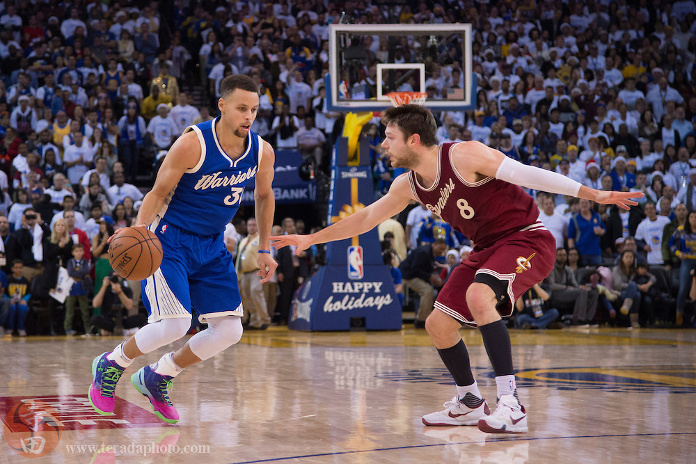 December 25, 2015; Oakland, CA, USA; Golden State Warriors guard Stephen Curry (30) dribbles the basketball against Cleveland Cavaliers guard Matthew Dellavedova (8) during the fourth quarter in a NBA basketball game on Christmas at Oracle Arena. The Warriors defeated the Cavaliers 89-83.
