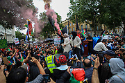 """Afghan woman carries a red flare during a protest """"Save Afghanistan"""" to protest the resurgence of the Taliban outside Downing Street, Britain's PM Office in central London on Saturday, Aug 21, 2021. (VX Photo/ Vudi Xhymshiti)"""