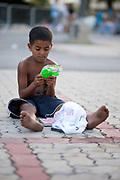Young Brazilian boy looking at a toy he was given from donations. In April 2014 thousands of people were evicted from Telerj favela in an old building owned by communications company Oi. Having nowhere to go, they camped outside the Central Cathderal in Rio de Janeiro, Brazil. Many of them were children, they received many donations from local people and community groups.