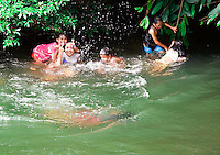 Iban kids swimming in the river after school at Nanga Sumpa Longhouse, Sarawak.