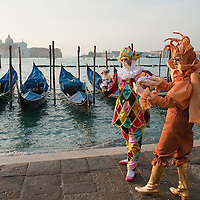 VENICE, ITALY - FEBRUARY 18:  A woman and a man dressed with carnival costume pose for pictures on February 18, 2012 in Venice, Italy.  The annual festival, which lasts nearly three weeks, will see the streets and canals of Venice filled with people wearing highly-decorative and imaginative carnival costumes and masks.  (Photo by Marco Secchi/Getty Images)