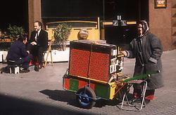 Street scene in Madrid showing barrel organ and shoe shine stall,