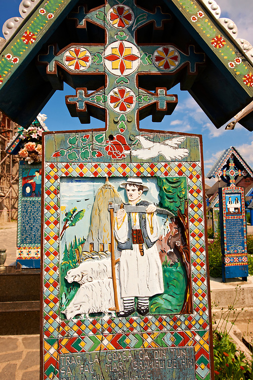 Tombstone of a shepherd and his sheep,  The  Merry Cemetery ( Cimitirul Vesel ),  Săpânţa, Maramares, Northern Transylvania, Romania.  The naive folk art style of the tombstones created by woodcarver  Stan Ioan Pătraş (1909 - 1977) who created in his lifetime over 700 colourfully painted wooden tombstones with small relief portrait carvings of the deceased or with scenes depicting them at work or play or surprisingly showing the violent accident that killed them. Each tombstone has an inscription about the person, sometimes a light hearted  limerick in Romanian. .<br /> <br /> Visit our ROMANIA HISTORIC PLACXES PHOTO COLLECTIONS for more photos to download or buy as wall art prints https://funkystock.photoshelter.com/gallery-collection/Pictures-Images-of-Romania-Photos-of-Romanian-Historic-Landmark-Sites/C00001TITiQwAdS8