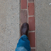 Legs walking down the Freedom trail red bricks in Boston, MA