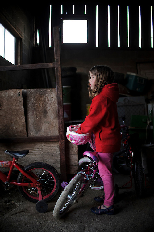 photo by Matt Roth.Wednesday, April 11, 2012..Rory Shriver finds her bicycle and helmet in her grandparents' barn...Ron Shriver grew up on a large farm house in Pleasant Valley, Maryland, a small township outside Westminster. After his lease was up, he moved back to his parent's home with his two children Rory and Miles, living temporarily in their basement before graduating from McDaniel College in May. After tossing his graduation cap, he and his children will drive cross country to meet up with his wife who has been working on her graduate degree in Alaska. ..Ron Shriver is a retired marine staff sergeant. He is also the first in his family to attend college, thanks to the New G.I. Bill. His wife, a fellow retired Marine, is finishing up graduate school in Alaska. After Ron gets his undergraduate degree from McDaniel College in May, he plans to drive to Alaska with is two children Rory, 6, and Miles, 5. For the move Ron got rid of most of his family's belongings, and after his lease was up, he and his children moved back into his parent's farmhouse.