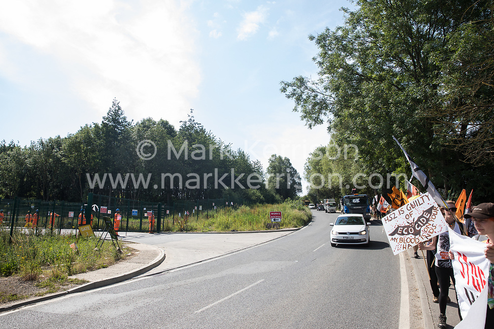 Harefield, UK. 26 June, 2020. Activists from HS2 Rebellion and Extinction Rebellion UK taking part in a 'Rebel Trail' hike along the route of the HS2 high-speed rail link from Birmingham to London protest opposite a gate to a HS2 construction site. The activists, who departed from Birmingham on 20th June and will arrive outside Parliament in London on 27th June, are protesting against the environmental impact of the high-speed rail link and questioning the viability of the £100bn+ project.