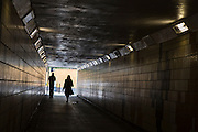 Pedestrians walk through a undepass in Romford, Essex.
